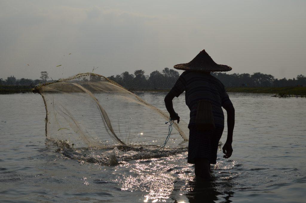 A Fisherman fishing in Community pond in Barnauli